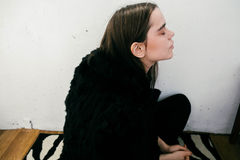 Девушка в черном пальто против белой стены Стоковое фото RF