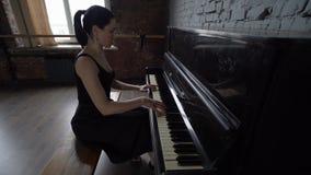 Девушка в черном платье сидит и играет рояль - замедленное движение сток-видео
