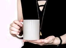 Девушка в черном платье держит белую чашку в руках Стоковые Изображения RF