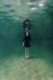 Девушка в черном платье подводном стоковая фотография
