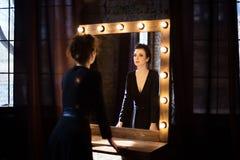 Девушка в черном платье смотря в зеркале Стоковое Изображение