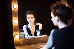 Девушка в черном платье смотря в зеркале Стоковая Фотография RF