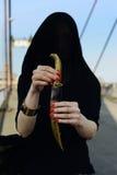 Девушка в черноте с восточным кинжалом Стоковая Фотография