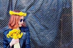 Девушка в черных куртке и шляпе с букетом одуванчиков Стоковое Изображение
