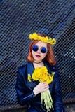 Девушка в черных куртке и шляпе с букетом одуванчиков Стоковые Фотографии RF