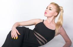 Девушка в черных одеждах, которая лежит на белой предпосылке Стоковая Фотография RF