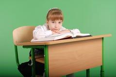 Девушка в школьной форме сидя на столе и читая книгу Стоковые Фото