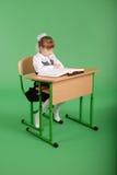 Девушка в школьной форме сидя на столе и читая книгу Стоковые Фотографии RF