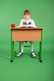 Девушка в школьной форме сидя на столе и читая книгу Стоковые Изображения