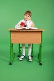 Девушка в школьной форме сидя на столе Стоковые Изображения RF