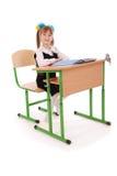 Девушка в школьной форме сидя на столе Стоковые Фото
