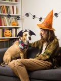 Девушка в шляпе ведьмы хеллоуина сидит при ее собака одеванная для партии хеллоуина Стоковая Фотография