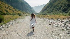 Девушка в шляпе идет вдоль середины дороги к горам Стоковые Изображения RF