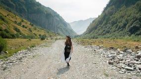 Девушка в шляпе идет вдоль середины дороги к горам Стоковое фото RF