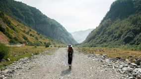 Девушка в шляпе и ботинки, прогулки в середине дороги против фона гор Стоковые Изображения RF