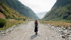 Девушка в шляпе и ботинки, прогулки в середине дороги против фона гор Стоковое Фото