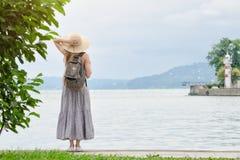 Девушка в шляпе при рюкзак стоя на пристани на море Горы и маяк на предпосылке задний взгляд Стоковые Изображения RF