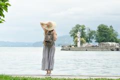 Девушка в шляпе при рюкзак стоя на пристани на море Горы и маяк на предпосылке Стоковая Фотография RF