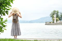 Девушка в шляпе при рюкзак стоя на пристани на море Горы и маяк на предпосылке задний взгляд Стоковое Фото