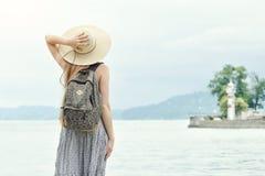 Девушка в шляпе при рюкзак стоя на пристани на море Горы и маяк на предпосылке Стоковая Фотография