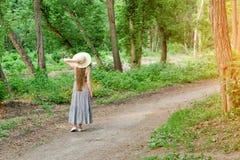 Девушка в шляпе стоит в лесе на пути в лесе назад осматривает Стоковое фото RF