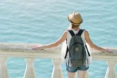 Девушка в шляпе стоя на балконе и смотря море вакханические стоковые фото
