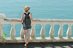 Девушка в шляпе стоя на балконе и смотря море вакханические стоковая фотография