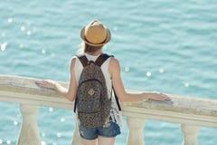 Девушка в шляпе стоя на балконе и смотря море вакханические стоковое фото