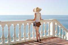 Девушка в шляпе стоя на лестницах и смотря море вакханические стоковое фото
