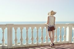 Девушка в шляпе стоя на лестницах и смотря море вакханические стоковые изображения