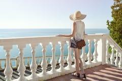 Девушка в шляпе стоя на лестницах и смотря море вакханические стоковое изображение rf