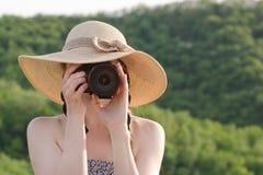 Девушка в шляпе фотографирует на фоне зеленого леса Стоковое Изображение