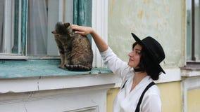 Девушка в шляпе штрихуя кота с ее рукой видеоматериал