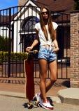 Девушка в шортах белого жилета и джинсов представляет с Стоковые Фотографии RF