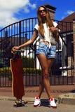 Девушка в шортах белого жилета и джинсов представляет с Стоковая Фотография RF