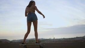 Девушка в шортах и тапки skateboarding вдоль дороги на предпосылке океана и гор акции видеоматериалы