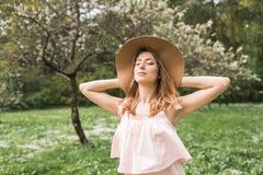 Девушка в шляпе и платье в саде стоковое фото rf