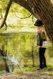 Девушка в шляпе идя в летний день парка и рыбную ловлю ручки в реке Стоковая Фотография RF