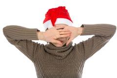 Девушка в шляпе santa закрывает сторону ладоней Стоковая Фотография