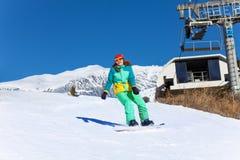 Девушка в лыжной маске сползая на сноуборд Стоковое Фото