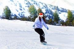 Девушка в лыжной маске сползая с сноубордом стоковое изображение