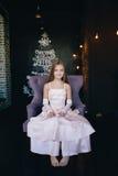 Девушка в элегантном платье сидя в стуле на предпосылке украшений рождества Стоковые Изображения