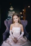 Девушка в элегантном платье сидя в стуле на предпосылке украшений рождества Стоковые Фотографии RF