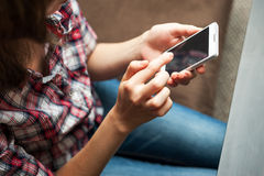 Девушка в checkered запись на ленту рубашки в сотовом телефоне стоковое фото rf