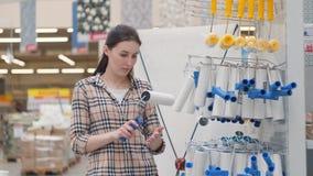Девушка в checkered рубашке в магазине, выбирает ролик для того чтобы покрасить сток-видео
