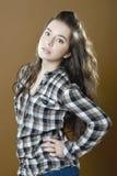 Девушка в checkered рубашке на коричневой (оранжевой) предпосылке Стоковое фото RF