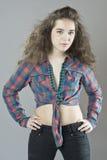 Девушка в checkered рубашке на коричневой (оранжевой) предпосылке Стоковое Изображение