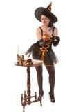 Девушка в costume ведьмы Halloween подготовляет зелье Стоковые Изображения