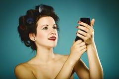 Девушка в curlers вводя волосы в моду смотря в зеркале Стоковое Изображение