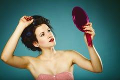 Девушка в curlers вводя волосы в моду смотря в зеркале Стоковая Фотография RF